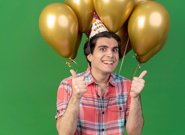 Un bell'uomo caucasico allegro che indossa un berretto di compleanno si trova di fronte a palloncini di elio con due mani in alto