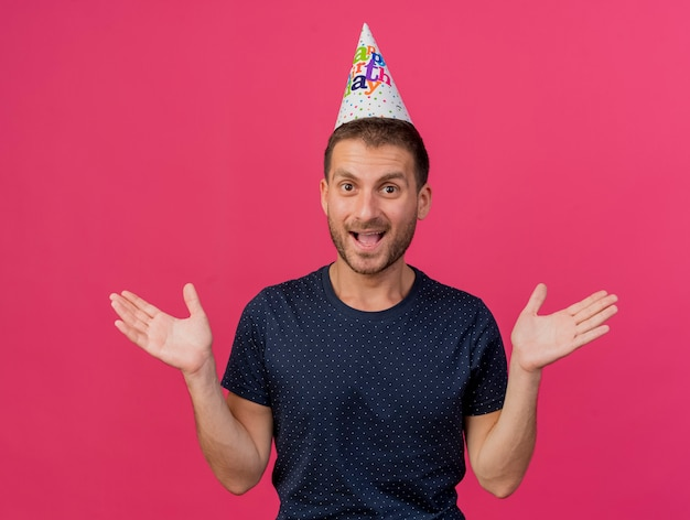 誕生日の帽子をかぶってうれしそうなハンサムな白人男性は、コピースペースでピンクの背景に分離された上げられた手で立っています