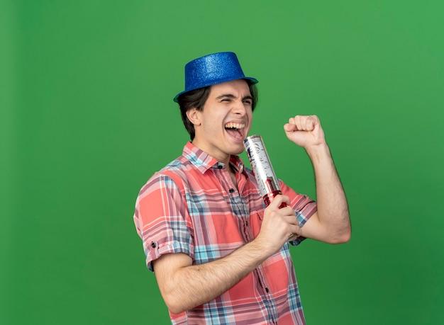 파란색 파티 모자를 쓰고 즐거운 잘 생긴 백인 남자는 색종이 대포를 보유하고 주먹을 유지