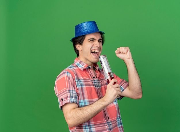 Joyful handsome caucasian man wearing blue party hat holds confetti cannon and keeps fist