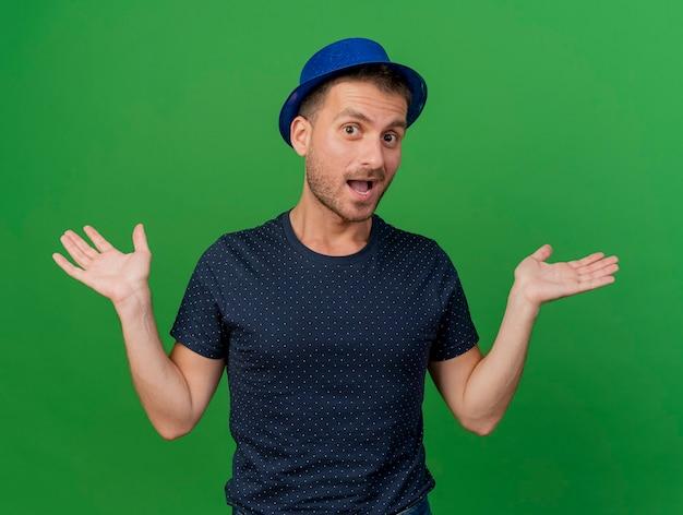 青いパーティー帽子をかぶってうれしそうなハンサムな白人男性は、コピースペースで緑の背景に分離された手を開いて保持します。