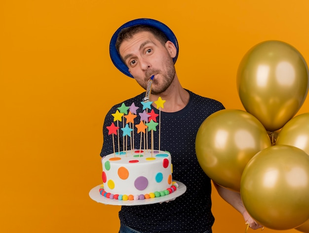 Gioioso bell'uomo caucasico che indossa il cappello blu del partito tiene palloncini di elio e torta di compleanno che soffia fischio isolato su sfondo arancione con spazio di copia