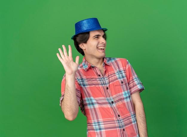青いパーティー ハットをかぶったうれしそうなハンサムな白人男性が、手を上げて側を見て立っています。