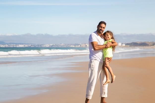 Gioioso papà bello che tiene la piccola figlia felice tra le braccia, in piedi sabbia bagnata, godendo del tempo libero con la ragazza sulla spiaggia in mare