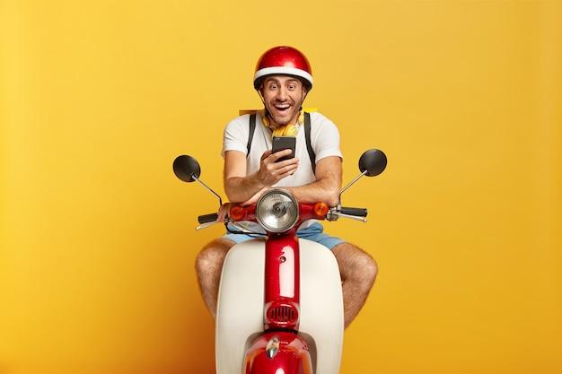Driver maschio bello gioioso su scooter con casco rosso