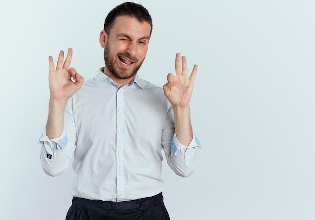 Радостный красавец моргает и жестикулирует знак рукой с двумя руками, изолированными на белой стене