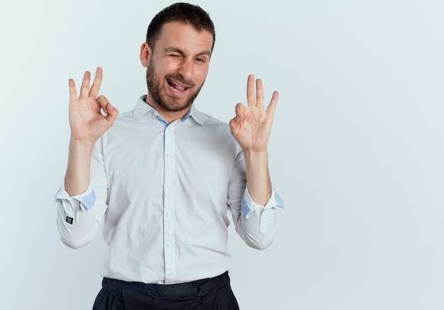 Gioioso bell'uomo sbatte le palpebre e gesti il segno giusto della mano con due mani isolate sul muro bianco
