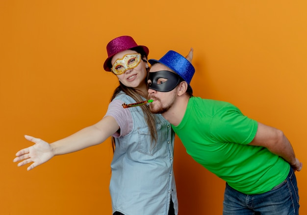 Joyful handsome man in blue hat wearing masquerade eye mask blowing whistle looking at side an surprised young girl wearing pink hat and masquerade eye mask pens arms looking