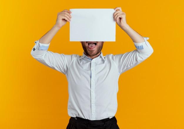 Gioioso bell'uomo tiene e chiude metà del viso con un foglio di carta isolato sulla parete arancione