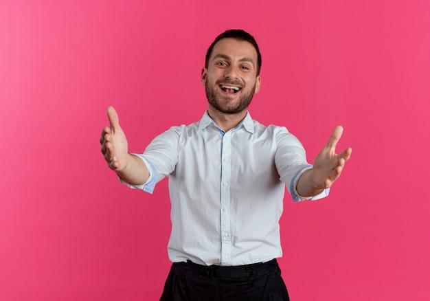L'uomo bello gioioso tiene fuori le mani isolate sulla parete rosa