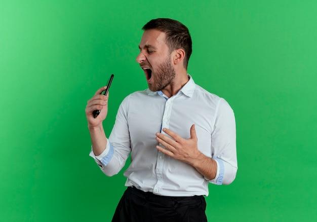 うれしそうなハンサムな男が電話を持って、緑の壁に孤立して歌うふりをして横を見る 無料写真
