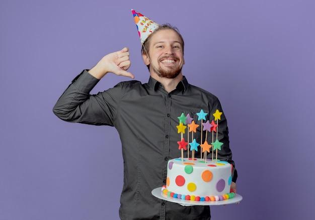 생일 모자에 즐거운 잘 생긴 남자가 보라색 벽에 고립 된 케이크를 보유하고 포인트
