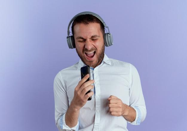 ヘッドフォンでうれしそうなハンサムな男は、紫色の壁に孤立して歌うふりをして電話を保持します。