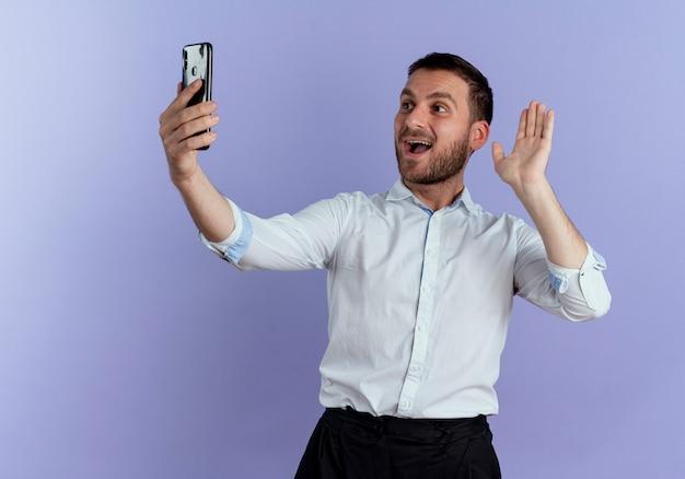 즐거운 잘 생긴 남자 손을 잡고 보라색 벽에 고립 된 전화를보고 제기