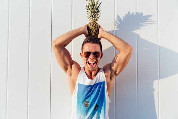 Joyful handsome man in sunglasses holds a pineapple on his head