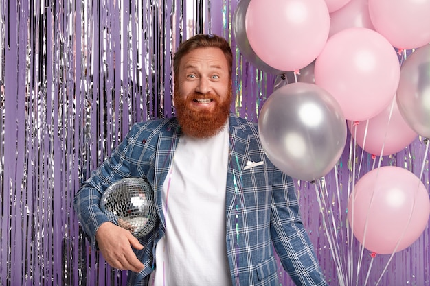 Joyful handsome man throws party after promotion at work, holds disco ball and bunch of air balloons, smiles happily, wears elegant jacket, stands over purple tinsel curtain, enjoys loud music