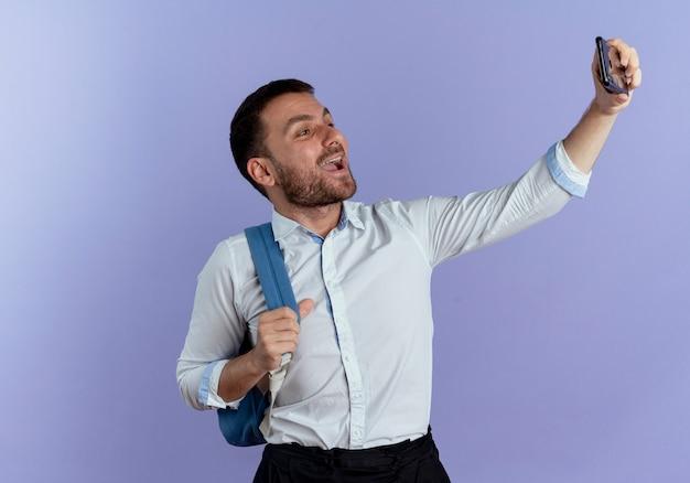 배낭을 입고 즐거운 잘 생긴 남자는 보라색 벽에 고립 된 셀카를 복용 전화를 보유하고