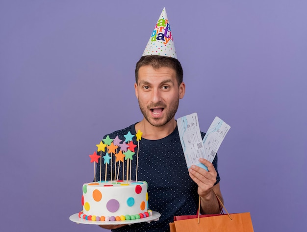 Joyful handsome man wearing birthday cap holds birthday cake paper shopping bag and air tickets isolated on purple wall with copy space