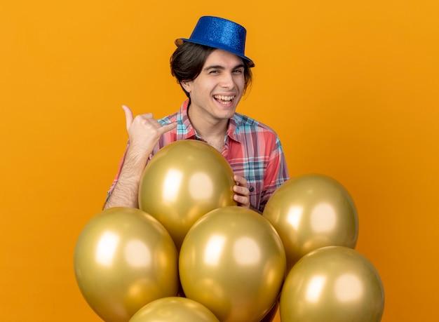 青いパーティーハットを身に着けているうれしそうなハンサムな男は、オレンジ色の壁に隔離されたサインを身振りで示すヘリウム気球で立っています