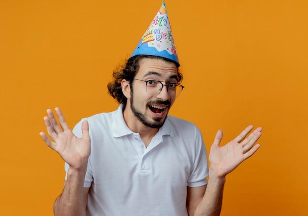 眼鏡と誕生日の帽子を身に着けているうれしそうなハンサムな男は、オレンジ色の背景に分離された手を広げます