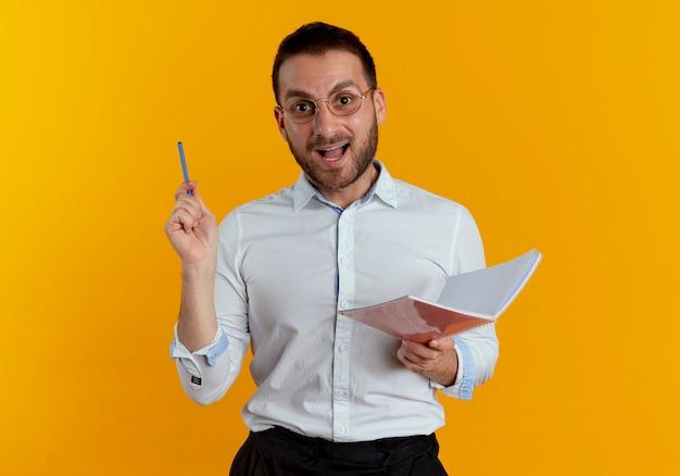 Gioioso bell'uomo con occhiali ottici tiene penna e taccuino isolato sulla parete arancione