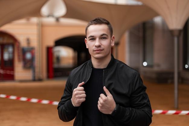 Радостный красивый молодой человек в черном стильном пиджаке и модной футболке позирует в городе