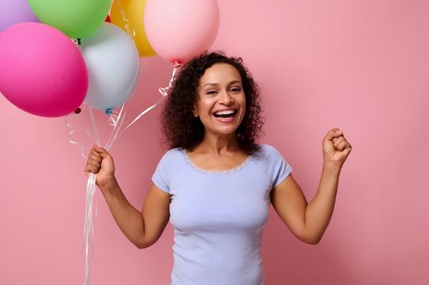 うれしそうな幸せなアフリカ系アメリカ人の女性は、彼女の手にカラフルな気球を持って、彼女の拳を握りしめ、カメラを見て、歯を見せる笑顔で微笑んで喜んでいます。記念日、お祝い、イベントのコンセプト