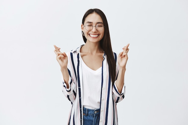 Joyful happy and carefree woman in glasses and striped blouse, smiling joyfully with closed eyes, being dreamy and thrilled while raising hands with crossed fingers, making wish