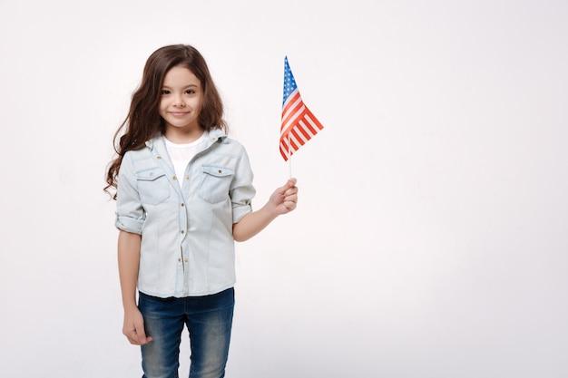 Радостная счастливая веселая девушка держит американский флаг, улыбаясь и стоя у белой стены