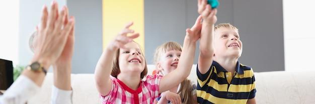 うれしそうな幸せな子供たちはボードホームゲームをします