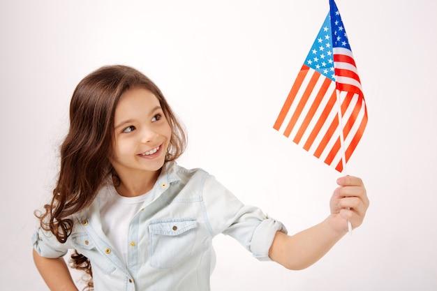 Радостная счастливая милая девушка держит американский флаг, выражая положительные эмоции и стоя у белой стены