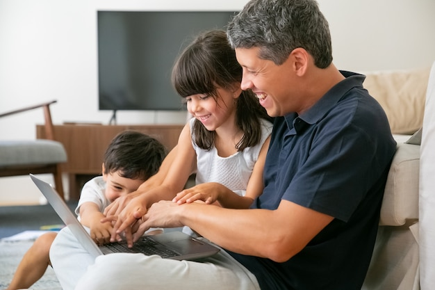 Joyful happy dad and two kids using laptop together, sitting on floor in apartment, pressing buttons in keyboards.