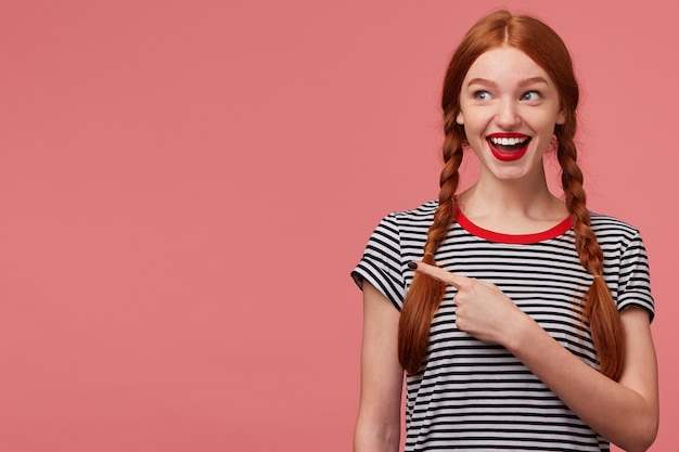 Joyful happy delighted inspired red haired teen girl with braids points with index finger on the empty space on left side, looking there and advises to pay attention, place for your advertisement