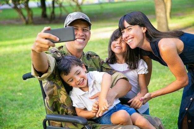 Радостный счастливый военный-инвалид, делающий селфи с женой и двумя детьми в парке. концепция семейного единения и поддержки
