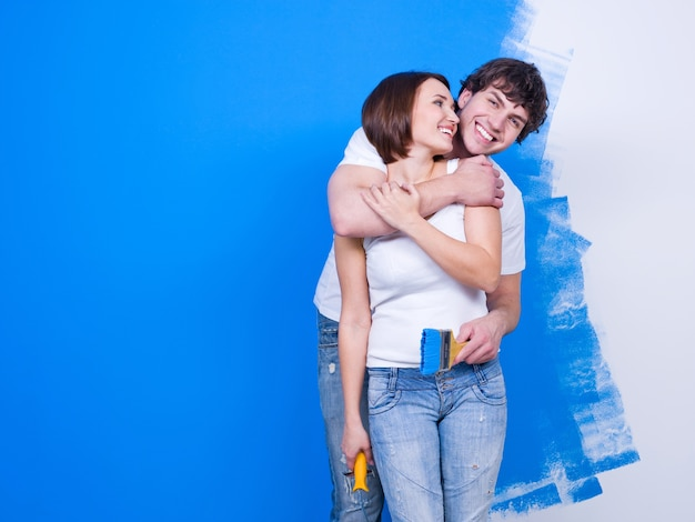Joyful happy embracing loving couple standing near the painted wall