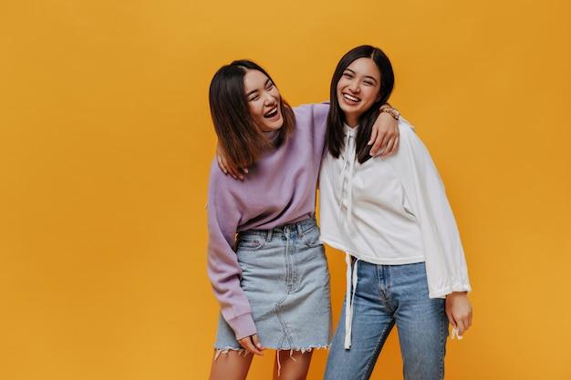 うれしそうな幸せな感情的な女の子はオレンジ色の壁で笑う