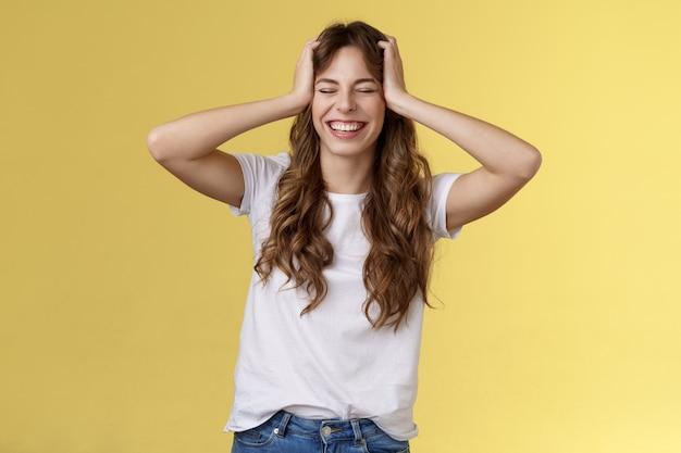 즐거운 행복한 열정적 인 잘 생긴 소녀는 믿을 수없는 멋진 기회를 얻습니다 해외 여행 여름 휴가 해외에서 머리를 감고 눈을 감고 행복하게 웃고 밝은 노란색 배경