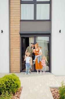Радостная счастливая семья, стоящая возле своего дома