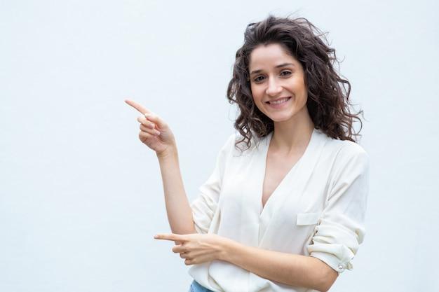 Joyful happy female customer pointing fingers away