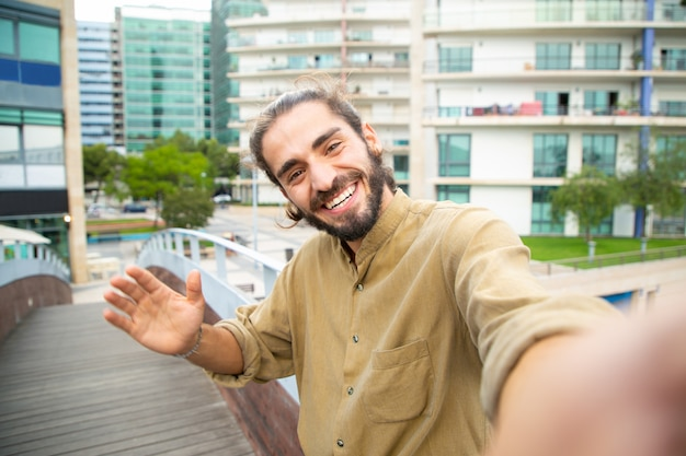 Joyful happy hipster guy taking selfie