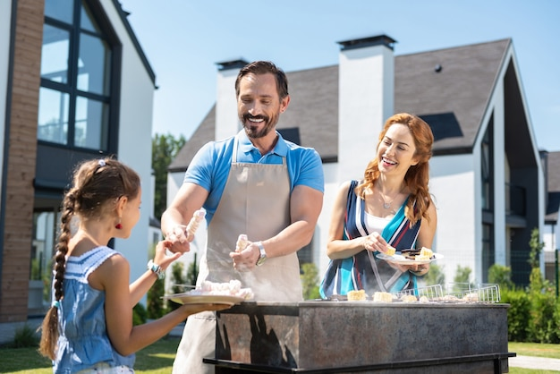 Joyful happy man holding marshmallows while having a picnic together with his family