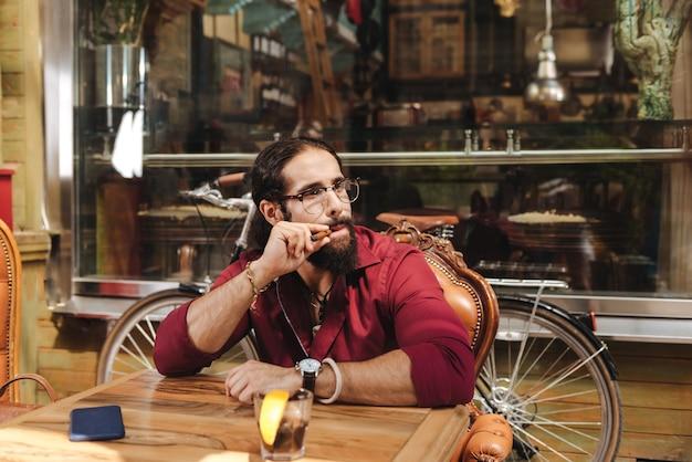 Радостный счастливый человек сидит за столом, наслаждаясь сигарой