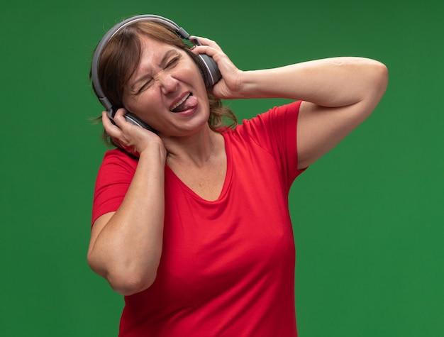 Donna di mezza età felice allegra in maglietta rossa con le cuffie che gode della sua musica preferita che attacca fuori la lingua che si leva in piedi sopra la parete verde
