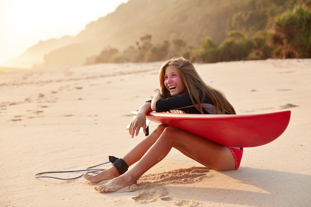 Joyful happy surfer laughs happily as being amused by friend, has zinc mask on face for safe surfing, uses board and leash