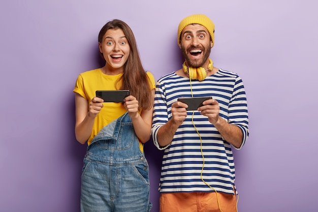 Joyful happy woman and man play games on smartphone, challenge each other, browse net