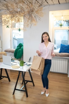 Joyful happy woman standing in the room with shopping bags after having successful shopping