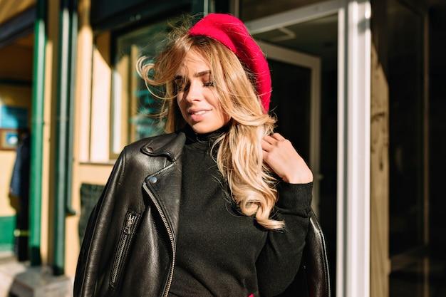 빨간 모자를 입은 물결 모양의 긴 금발 머리를 가진 즐거운 행복 한 여자는 데이트와 미소에 산책합니다. 맑은 소녀는 외부 생활을 즐깁니다.