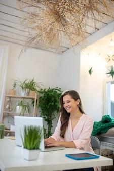 彼女の仕事を楽しみながら笑顔のうれしそうな幸せな若い実業家