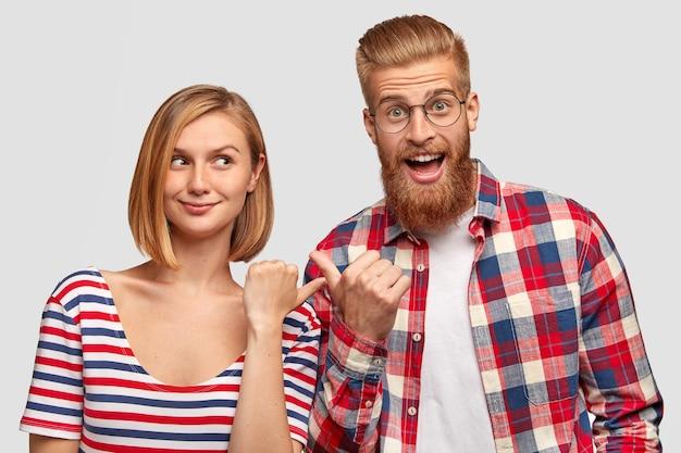 うれしそうな幸せな若いカップルは一緒に楽しんで、お互いに示し、幸せな表情を持って、白い壁に立ち向かう