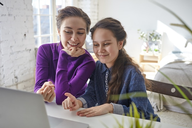 Joyful happy young mother and daughter shopping online using laptop pc, sitting at desk in light bedroom interior, pointing fingers at screen and smiling